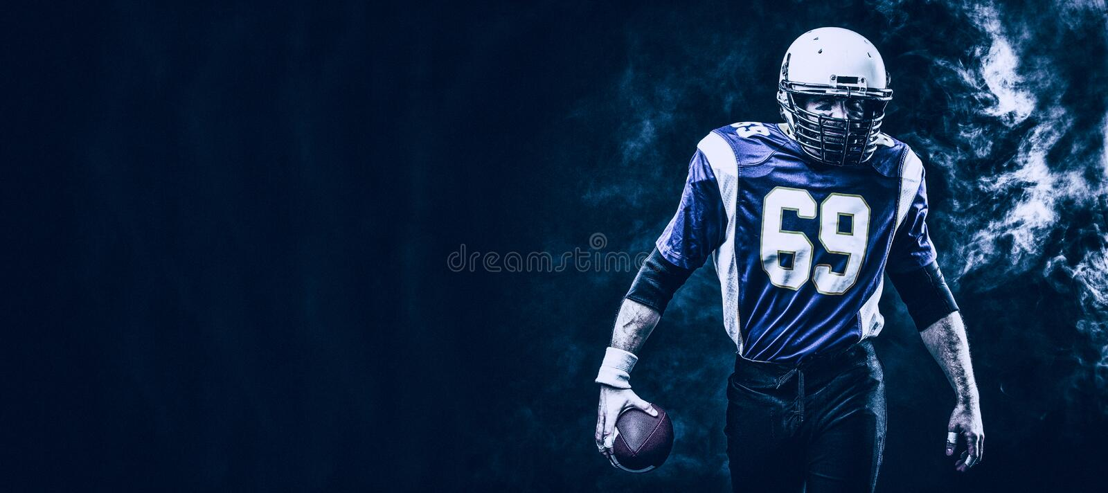 American football player holding ball in his hands in smoke. Black background, copy space. The concept of American stock images