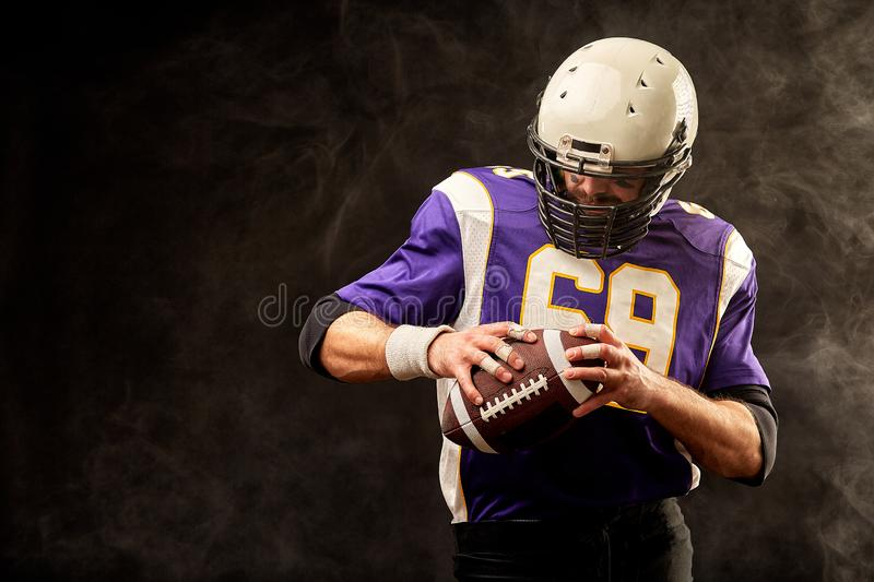 American football player holding ball in his hands in smoke. Black background, copy space. The concept of American stock photography