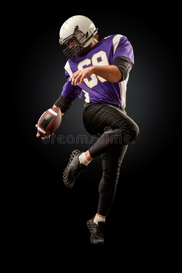 American football player holding a ball while jumping away from a strike. Black background, copy space. Violet with stock photography