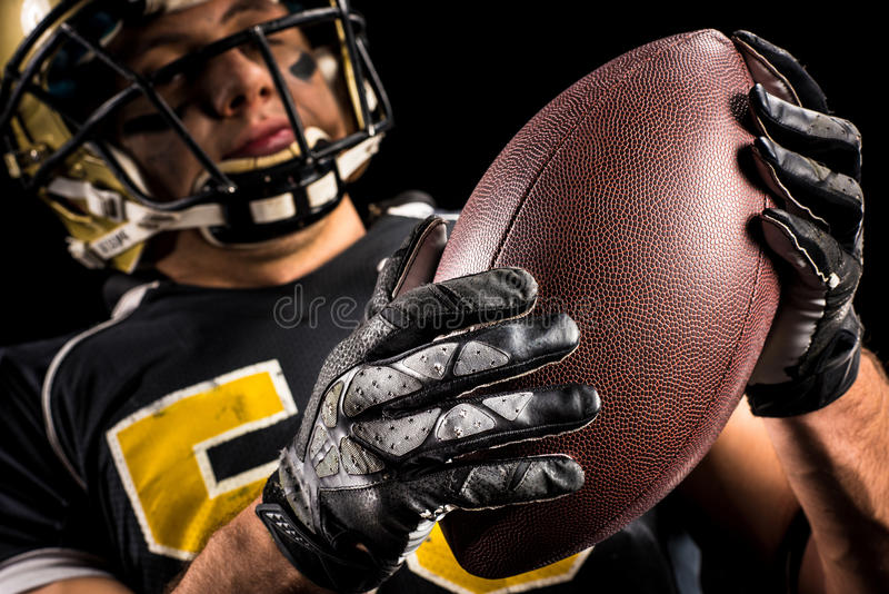 American football player holding ball stock images
