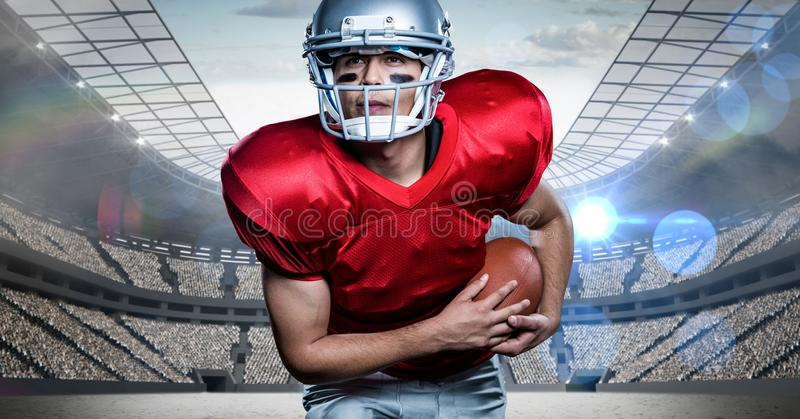 American football player holding rugby ball against stadium in background royalty free stock photography
