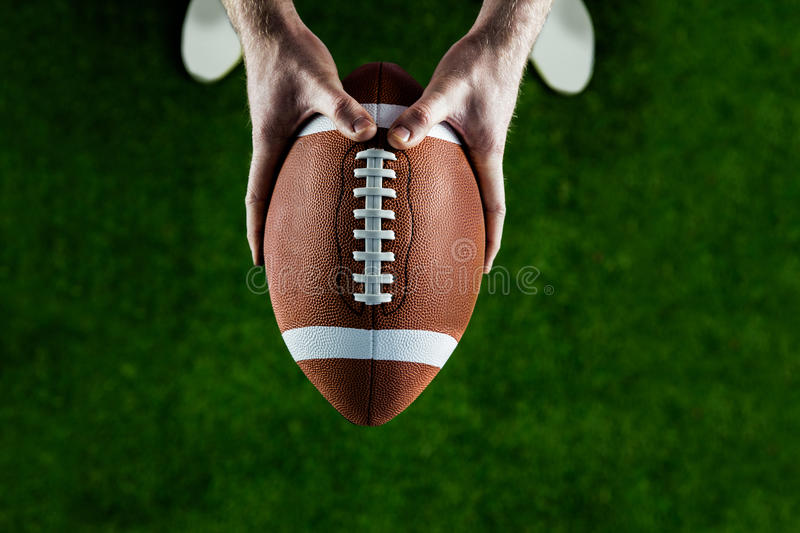American football player holding up football royalty free stock image