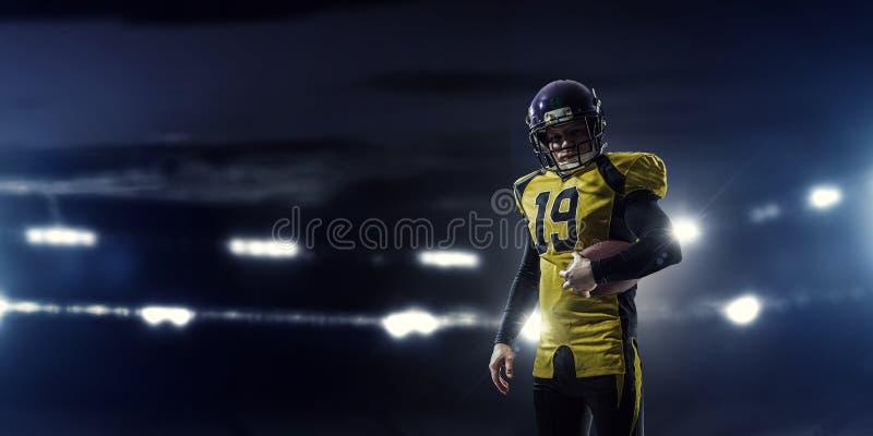 American football player . Mixed media. Confident American football player in lights of sport arena. Mixed media royalty free stock image