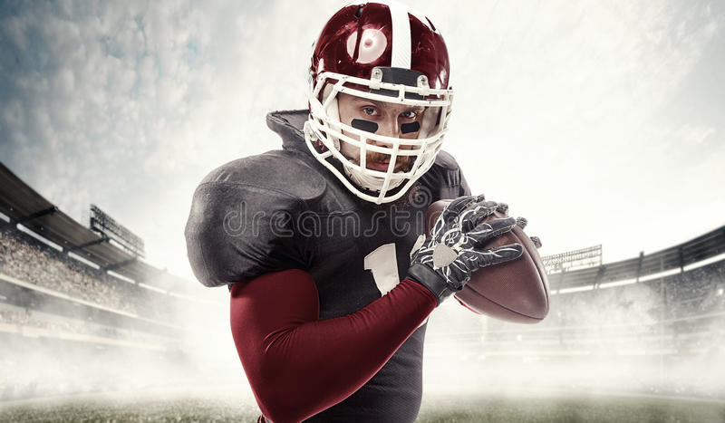 American football player posing with ball on stadium background stock photos