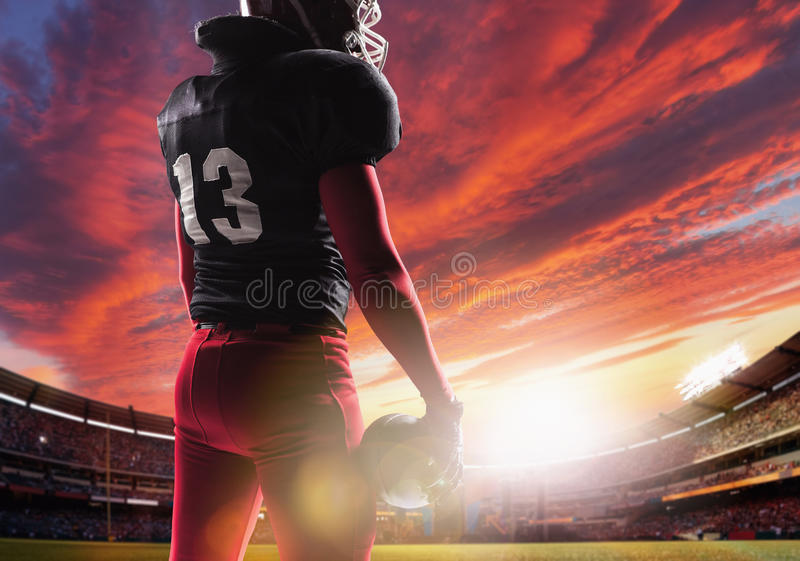 American football player posing with ball on stadium background stock photography