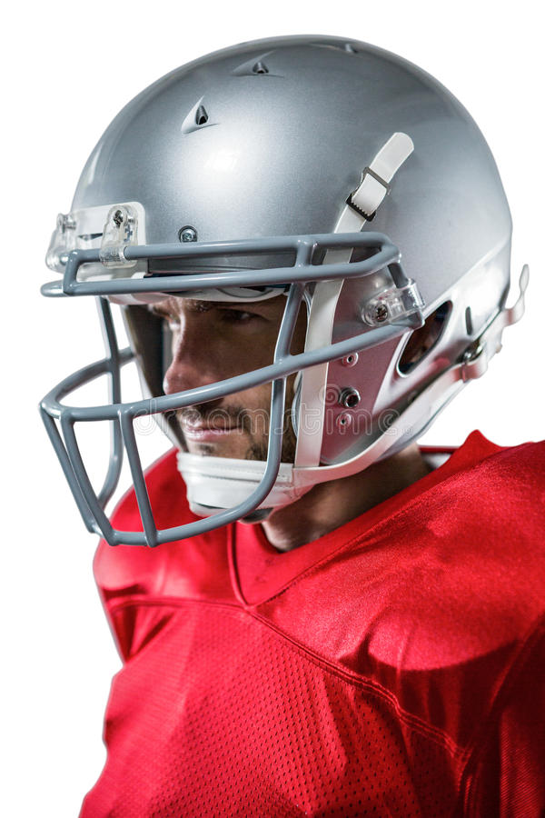 American football player in red jersey looking away. Close-up of American football player in red jersey looking away against white background stock photo