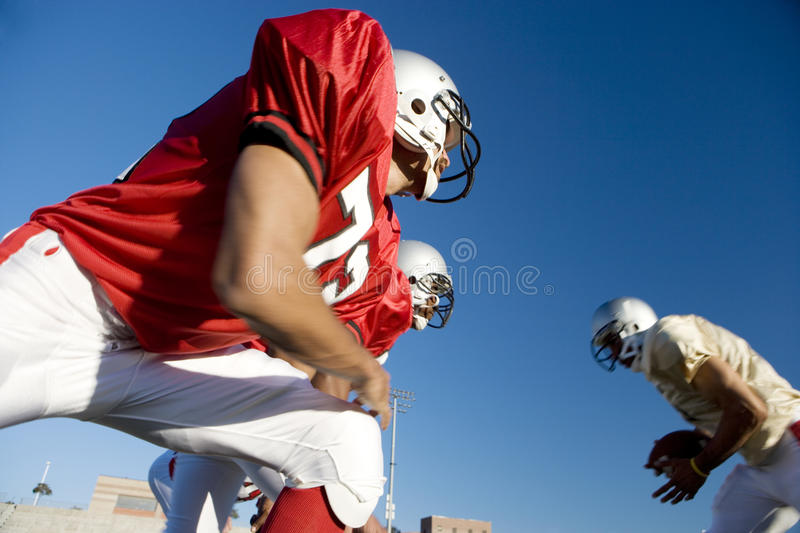 American football player running with ball at opposing team during competitive game, side view, low angle view.  stock photography