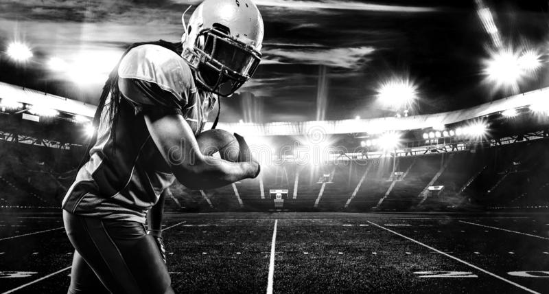American football player, athlete in helmet with ball on stadium. Black and white photo. Sport wallpaper with copyspace. royalty free stock photo