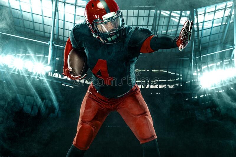 American football player, athlete sportsman in red helmet on stadium background. Sport and motivation wallpaper. royalty free stock photo