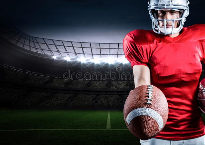 American football player standing with ball against digitally generated background royalty free stock images