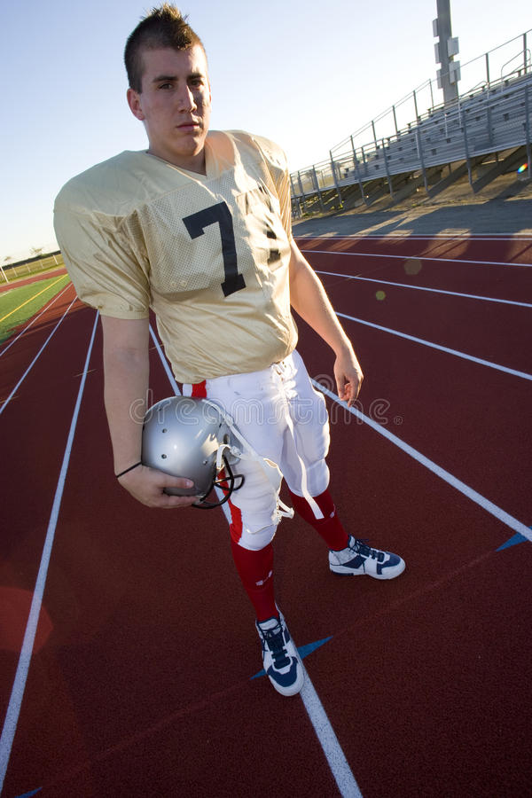 American football player standing on sports track, carrying protective helmet underarm, front view, portrait (tilt) stock image