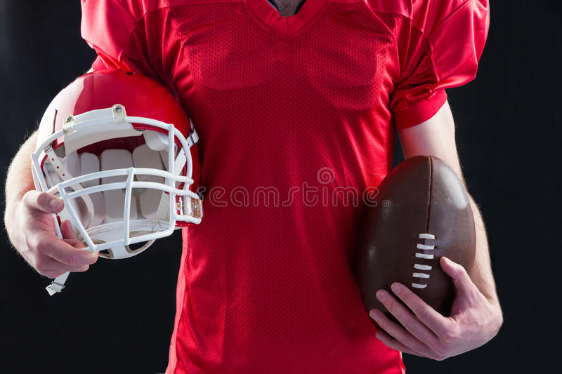 An american football player taking a helmet and ball in her hands stock images