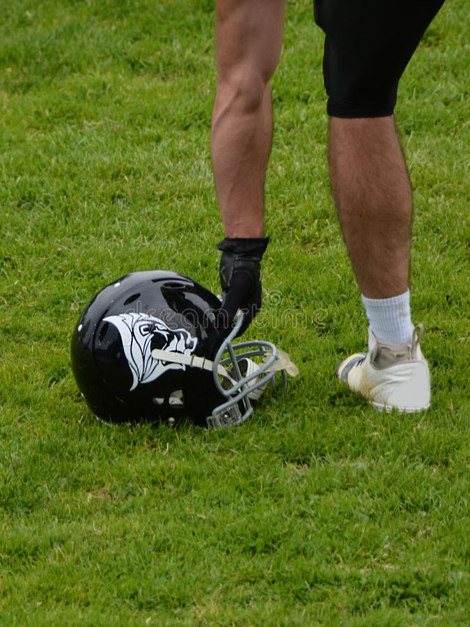 American football player taking helmet from the ground stock images