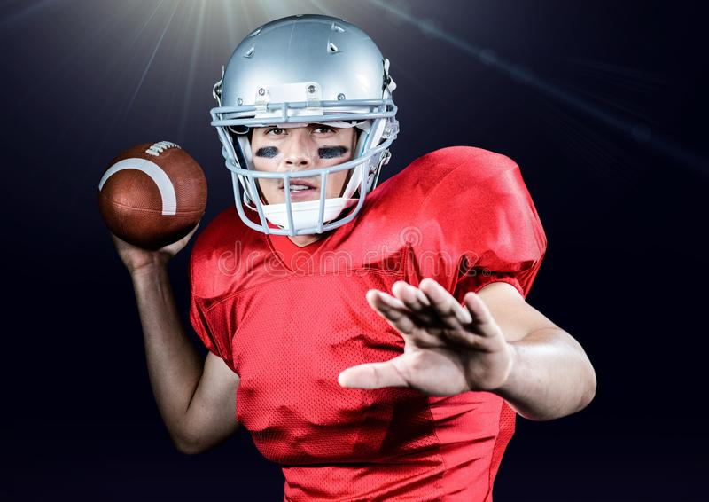 American football player throwing ball against black background royalty free stock photography