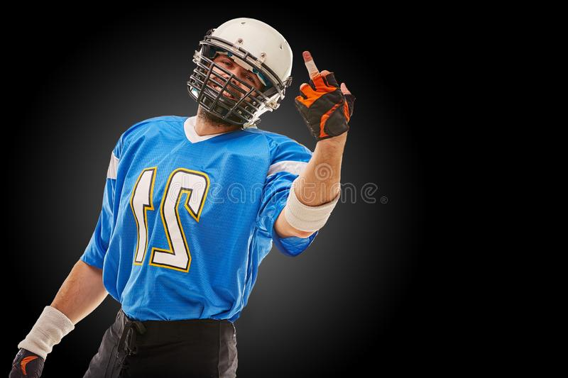 American football player in uniform shows hand fuck. American football, copy space, black background. royalty free stock images