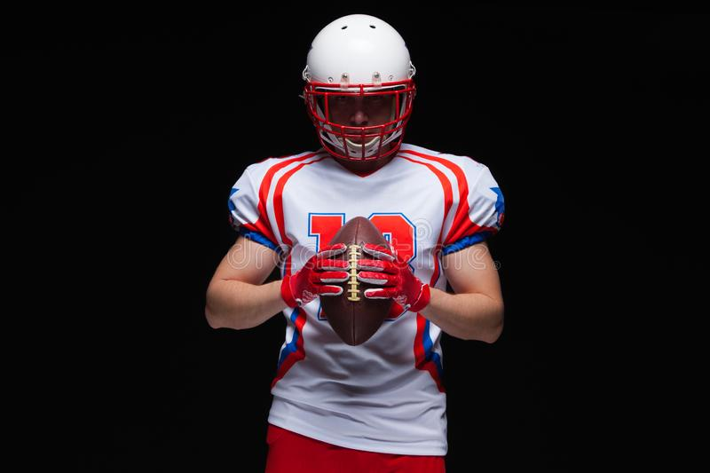 American football player wearing helmet holding ball in front of him on black background royalty free stock photos