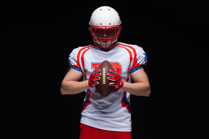 American football player wearing helmet holding ball in front of him on black background stock photos