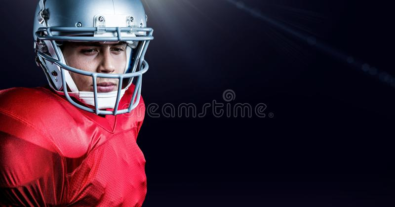 American football player wearing helmet standing against black background stock photography