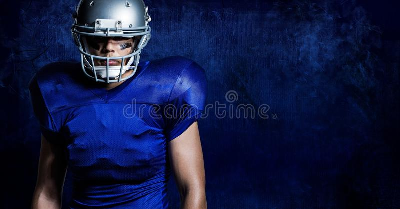 American football player wearing helmet standing against blue background stock photography