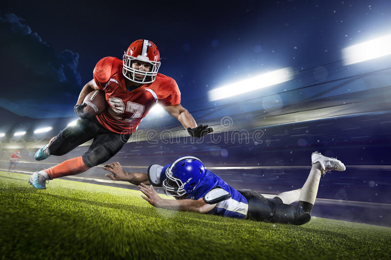 American football players in action on grand arena royalty free stock photography