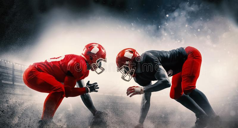 American football players in action play in professional sport stadium. Fit caucasian men in uniform with ball. Human emotions and facial expressions concept royalty free stock image
