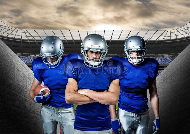 American football players standing against stadium in background stock images