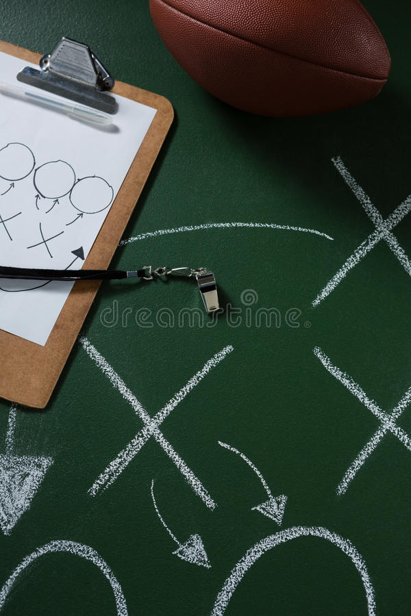 American football and referee whistle lying on green board with strategy drawn on it stock images