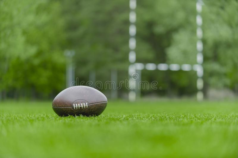 American football, rugby ball on green grass field background stock photography