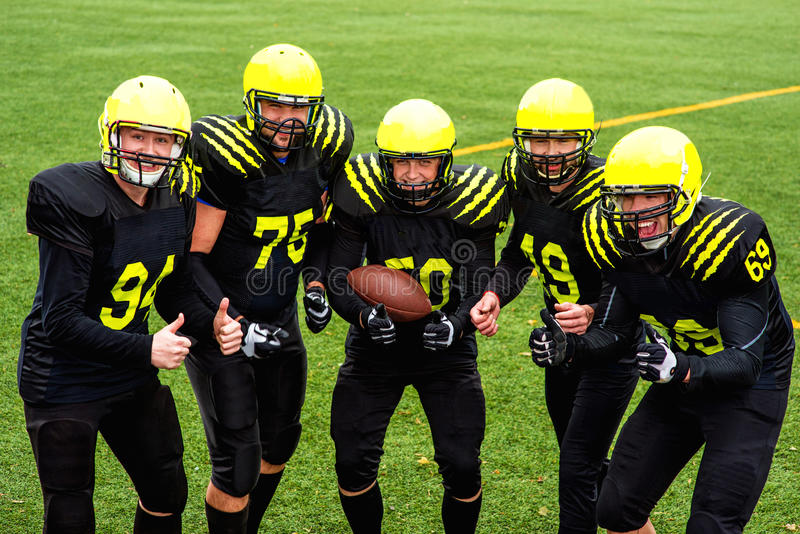 American football team. In sportswear with the ball standing together on the sports ground stock photography