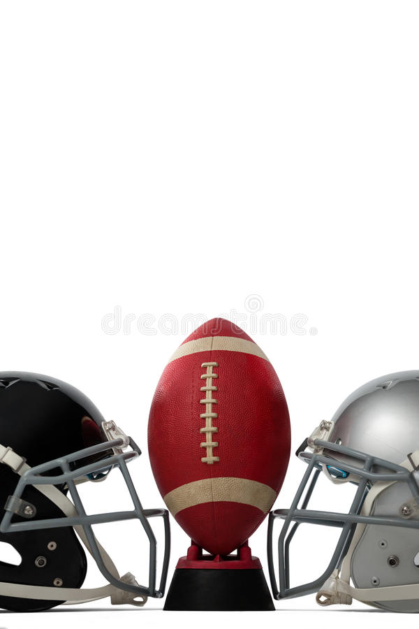 American football on tee by silver and black sports helmets. Against white baclground royalty free stock photography