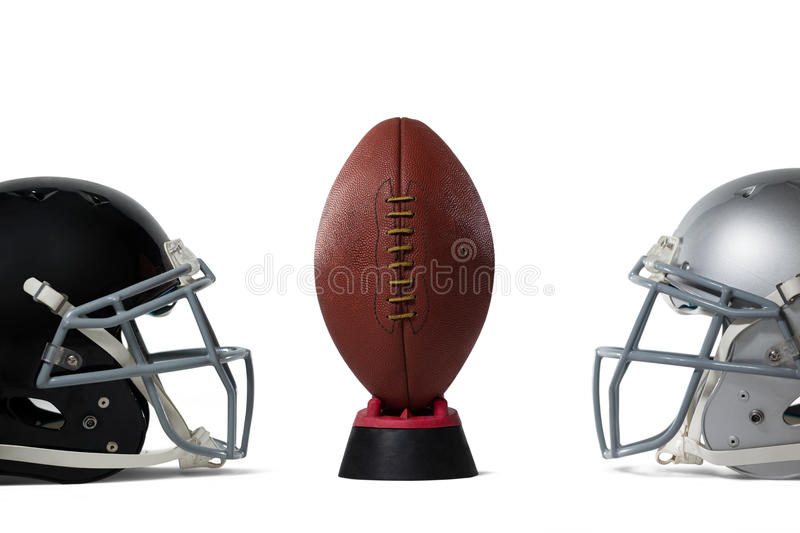American football on tee by sports helmets. Against white baclground royalty free stock images