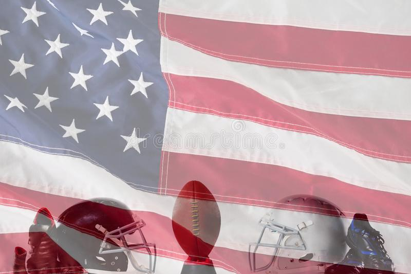 Composite image of american football on tee by sports shoes and helmets. American football on tee by sports shoes and helmets against close-up of an american stock images