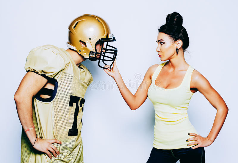 American football young man player in action. Little girl playing with big men in football. American football young men player in helmet. Young women playing stock photo