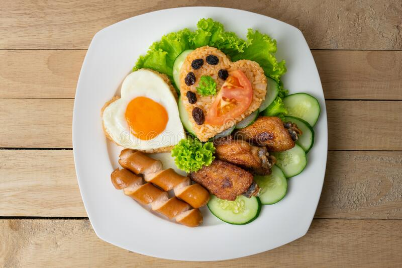American fried rice with cucumber and lettuce in white dish on wooden table.  royalty free stock photography