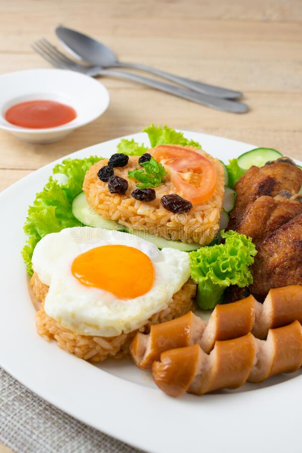 American fried rice with cucumber and lettuce in white dish on wooden table.  stock photography