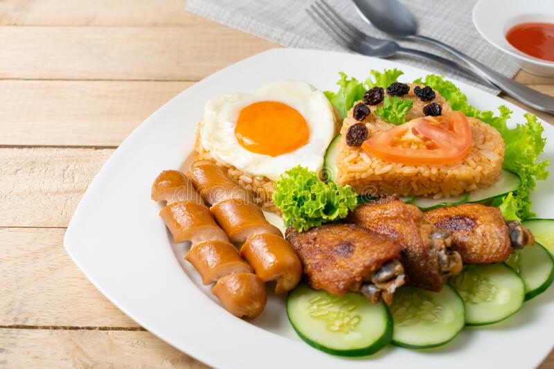 American fried rice with cucumber and lettuce in white dish on wooden table.  stock image