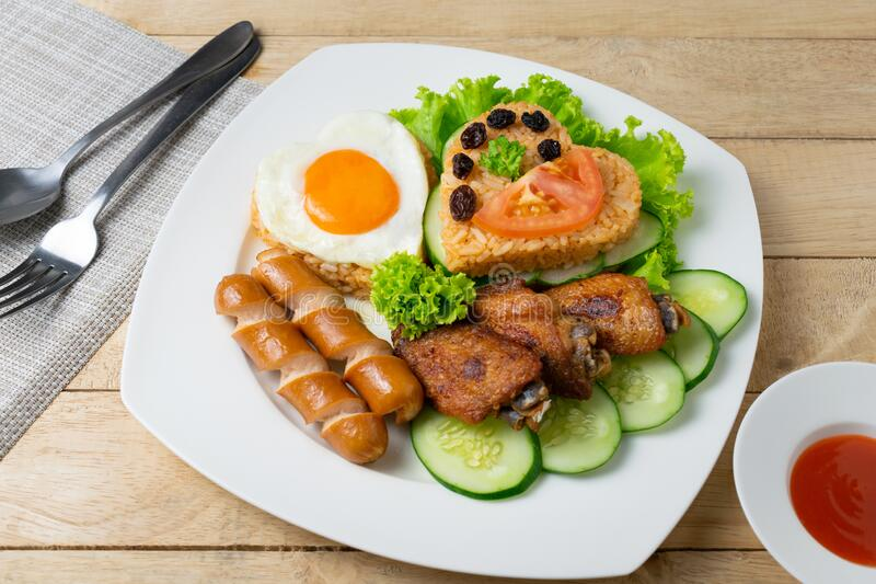 American fried rice with cucumber and lettuce in white dish on wooden table.  stock photo