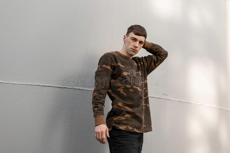 American handsome young man in fashionable military clothes with a stylish hairstyle poses near a metallic gray wall outdoors. Attractive guy on a walk on a stock photos
