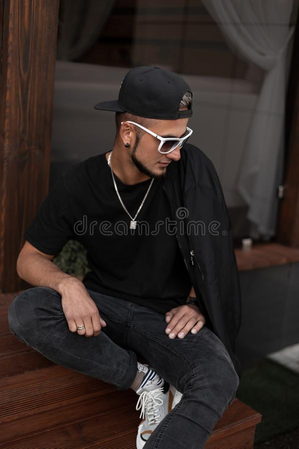 American hipster young man with a beard in a cap in a T-shirt in a jacket in sunglasses sits on wooden stairs near a vintage cafe royalty free stock photos