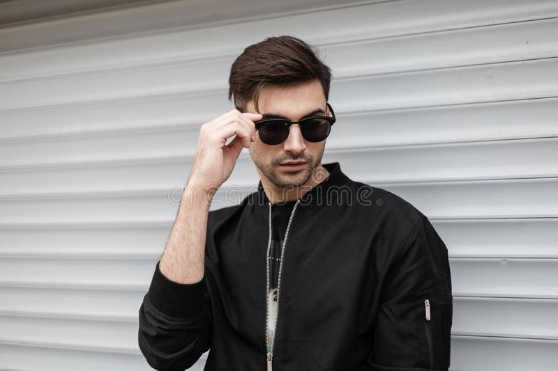 American hipster young man in a black stylish jacket stands and straightens trendy sunglasses near a metallic white wall royalty free stock image