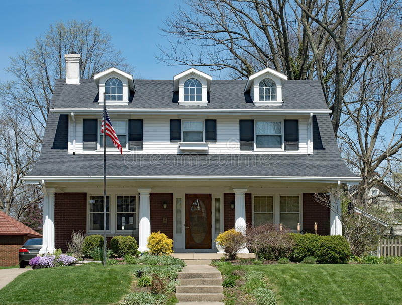 American Home with Dormers & Open Porch. Home with three dormers, open porch with stately columns & American flag royalty free stock photo