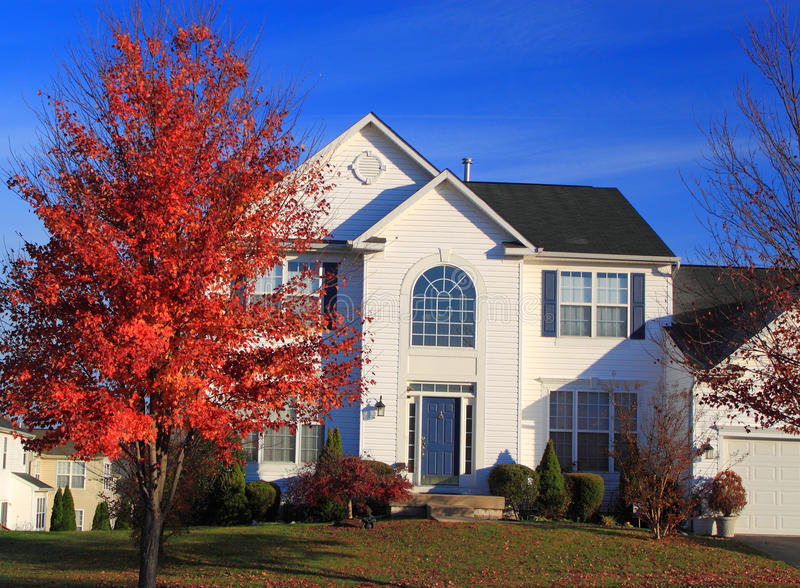 Two Story House Autumn. Two story home in autumn with high foyer, car garage, and tree and lawn royalty free stock photos