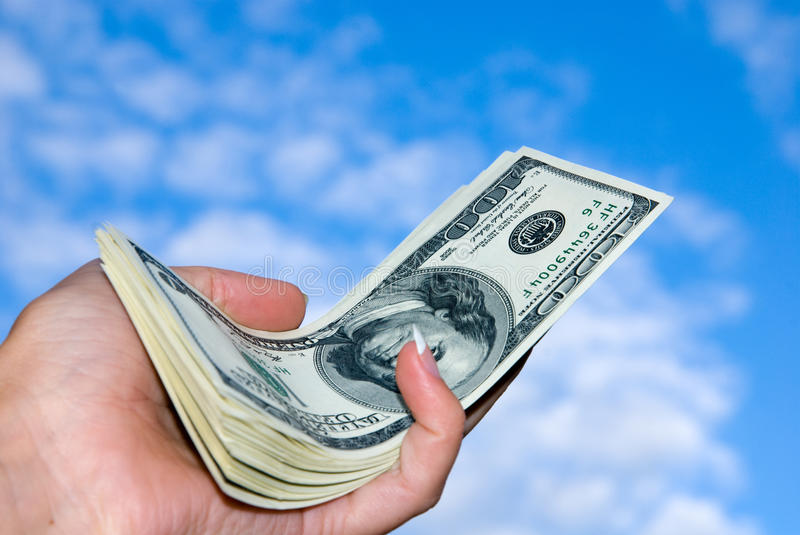 American hundred dollars bundle in the hand. Large american hundred dollars bundle in the hand against the blue sky stock images