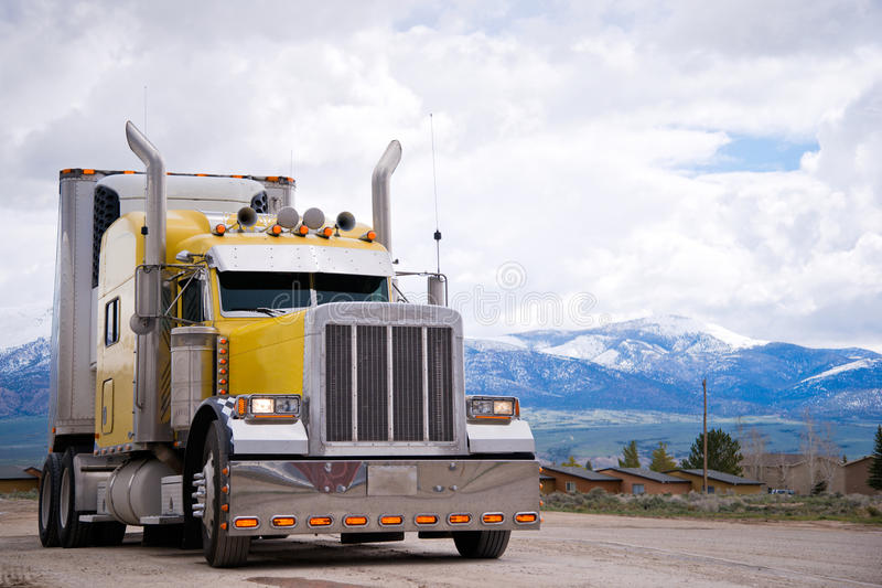 American icon of style customized yellow semi truck rig. Powerful yellow classic popular professional American bonneted big rig semi truck with chrome accents royalty free stock images