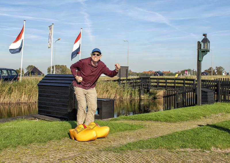 American male tourist posing in big yellow clogs by the Schermerhorn Museum Mill and visitors center, Stompetoren, Netherlands royalty free stock photo