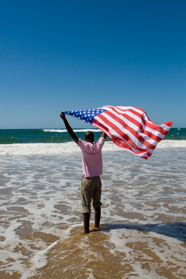American man and flag. Young african american man running with USA flag on beach stock images