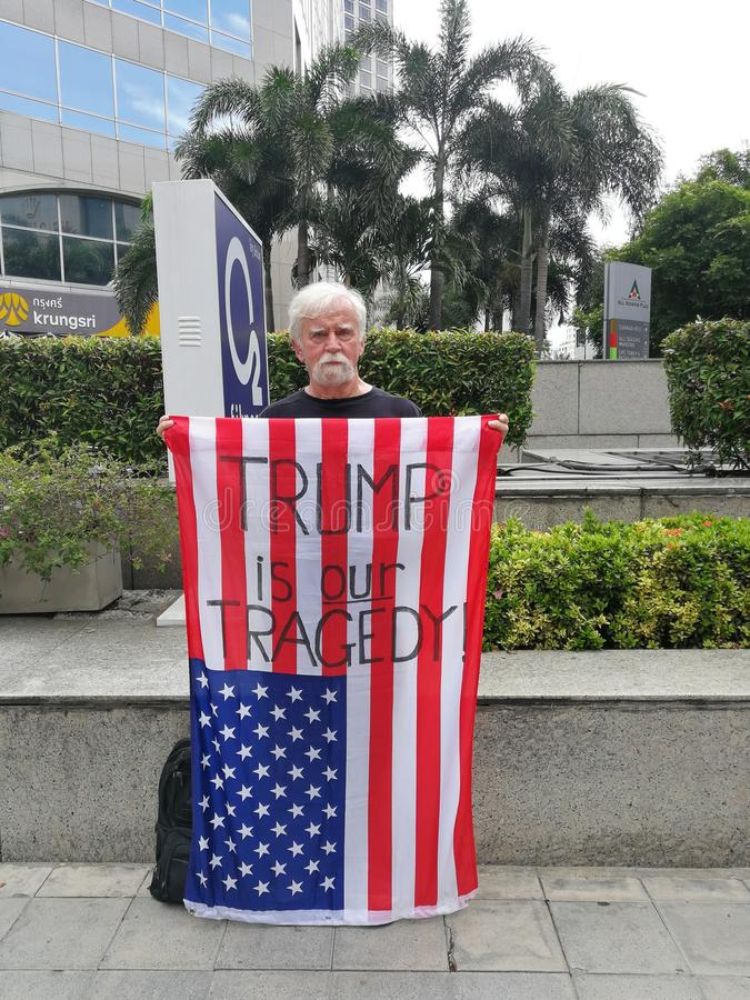 An American man show the American flag with the words `TRUMP IS OUR TRAGEDY.` On the Wireless road near the US embassy in Thailand royalty free stock image