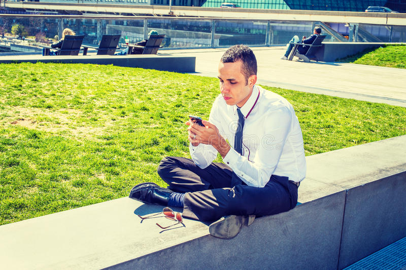 American Man Texting Outside in New York. American Businessman traveling, working in New York, wearing white shirt, black pants, leather shoes, sunglasses on royalty free stock image