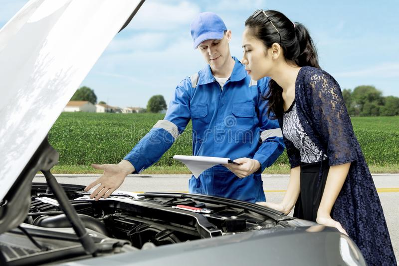 American mechanic with broken car and his customer stock photos