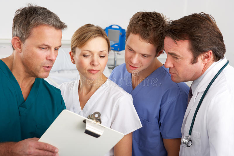 American medical team working on hospital ward. Discussing a patients chart stock photos